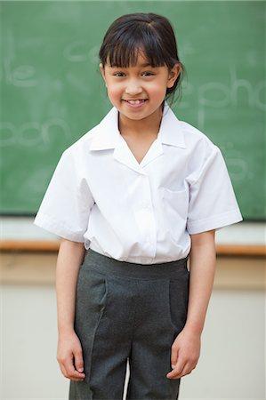 school girl uniforms - Smiling schoolgirl in front of blackboard Stock Photo - Premium Royalty-Free, Code: 6109-06196569