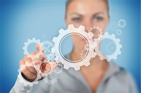 Businesswoman touching on wheels and cogs graphic Stock Photo - Premium Royalty-Free, Code: 6109-06684740