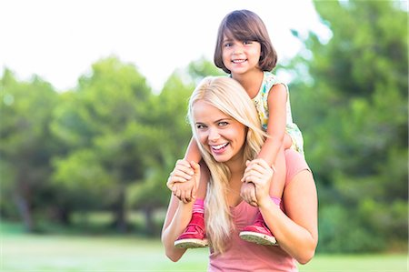 Beautiful mother giving daughter a piggy back Stock Photo - Premium Royalty-Free, Code: 6109-06684767
