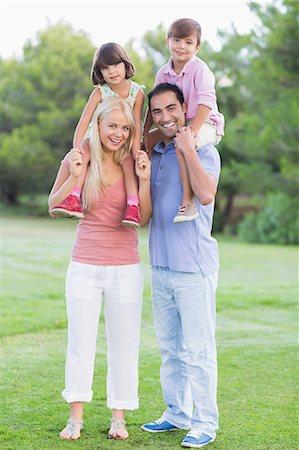 Portrait of parents giving children a piggy back Stock Photo - Premium Royalty-Free, Code: 6109-06684764