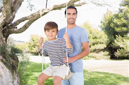 swing (sports) - Portrait of father pushing son on a swing Stock Photo - Premium Royalty-Free, Code: 6109-06684813