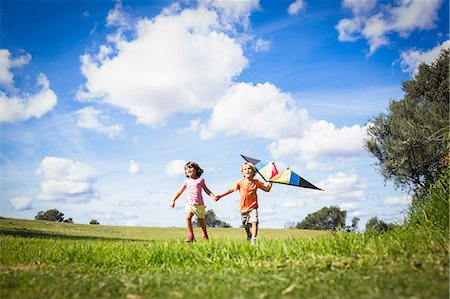 Brother and sister holding hands and playing with a kite Stock Photo - Premium Royalty-Free, Code: 6109-06684811