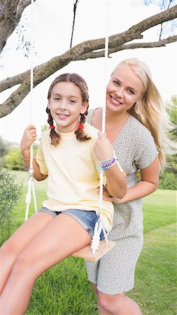 swing (sports) - Portrait of happy mother pushing her daughter on a swing Stock Photo - Premium Royalty-Free, Code: 6109-06684812