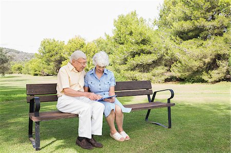 Elderly couple using tablet in the park Stock Photo - Premium Royalty-Free, Code: 6109-06684822
