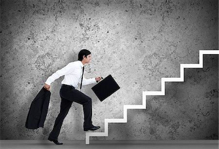 Businessman climbing the stairs to the top Stock Photo - Premium Royalty-Free, Code: 6109-06684997