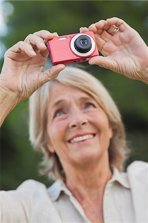 Older blonde woman taking a photo Stock Photo - Premium Royalty-Free, Code: 6109-06684911