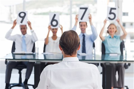 scoring - Panel of judges showing marks in front of an applicant Stock Photo - Premium Royalty-Free, Code: 6109-06781347