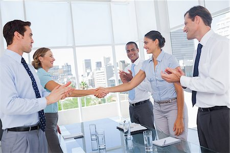 Business people clapping their hands between colleagues Stock Photo - Premium Royalty-Free, Code: 6109-06781357