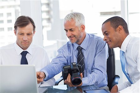 staff - Businessman holding a camera and pointing at the laptop Stock Photo - Premium Royalty-Free, Code: 6109-06781390
