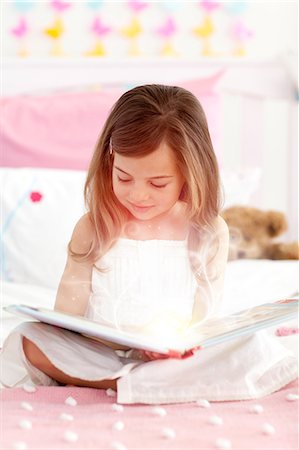 Little girl reading a storybook Stock Photo - Premium Royalty-Free, Code: 6109-06781329