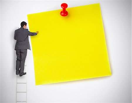 Businessman standing on ladder writing on large yellow note Stock Photo - Premium Royalty-Free, Code: 6109-06781462