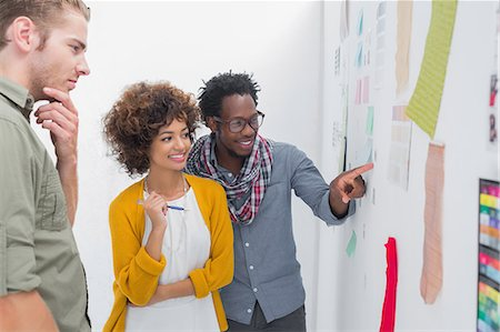 Smiling team of designers pointing at a wall Stock Photo - Premium Royalty-Free, Code: 6109-06781486