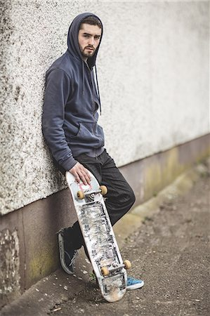 Skater leaning against wall Stock Photo - Premium Royalty-Free, Code: 6109-06781433