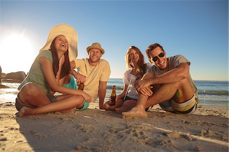 Laughing friends partying on the beach with beers Stock Photo - Premium Royalty-Free, Code: 6109-06781685
