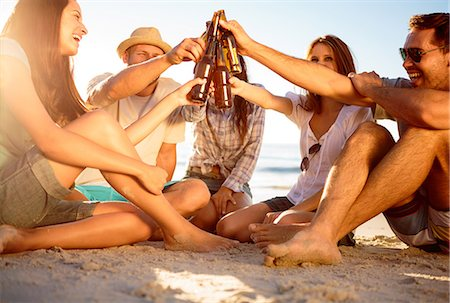 Friends clicking their bottles of beer on the beach Stock Photo - Premium Royalty-Free, Code: 6109-06781688