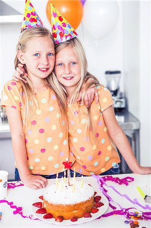 Twins looking at the camera on a birthday Stock Photo - Premium Royalty-Free, Code: 6109-06781756