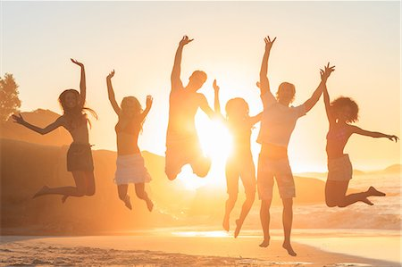 Young people jumping in front of the sunset Stock Photo - Premium Royalty-Free, Code: 6109-06781784
