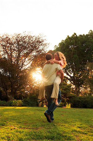 Man holding his girlfriend in a park Stock Photo - Premium Royalty-Free, Code: 6109-06781733