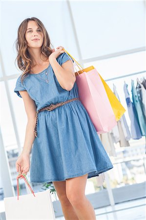 Pretty brunette holding shopping bags Stock Photo - Premium Royalty-Free, Code: 6109-06781972