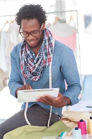 Smiling fashion designer working on a tablet Stock Photo - Premium Royalty-Free, Code: 6109-06781922