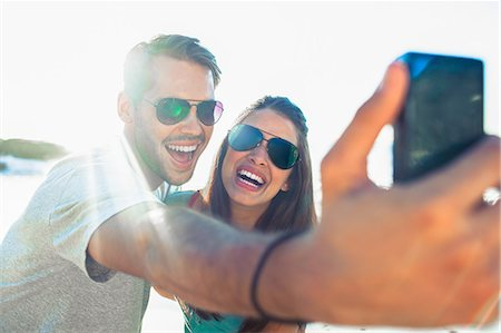 Young couple taking photo with camera on the beach Stock Photo - Premium Royalty-Free, Code: 6109-07496966