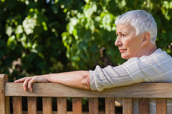 Pensive elderly woman sitting alone on a bench in a park Stock Photo - Premium Royalty-Free, Image code: 6109-07497002