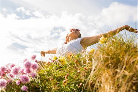 purple - Woman feeling free in field of wild flowers and looking up at sky with arms outstretched Stock Photo - Premium Royalty-Free, Code: 6109-07497039