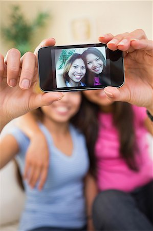 Two beautiful sisters taking a picture of themselves sitting on a white couch Stock Photo - Premium Royalty-Free, Code: 6109-07497163