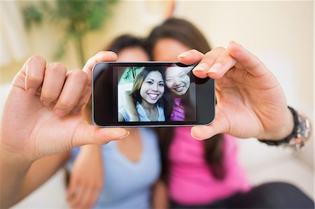 Two cute sisters taking a photo of themselves in the living room Stock Photo - Premium Royalty-Free, Code: 6109-07497162