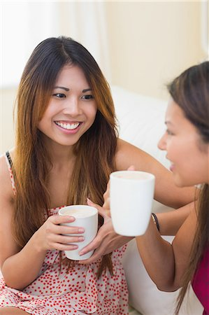 friend (female) - Two beautiful young sisters chatting and drinking a coffee while sitting in the living room Stock Photo - Premium Royalty-Free, Code: 6109-07497172