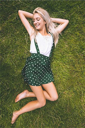 polka dot - Cheerful gorgeous blonde lying on lawn with closed eyes in bright sunlight Stock Photo - Premium Royalty-Free, Code: 6109-07497118