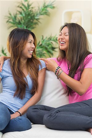 sister - Two laughing sisters sitting on a couch in the living room Stock Photo - Premium Royalty-Free, Code: 6109-07497137