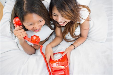 phone cord - Two sisters making a call on an old fashioned dial phone while lying on a bed Stock Photo - Premium Royalty-Free, Code: 6109-07497202