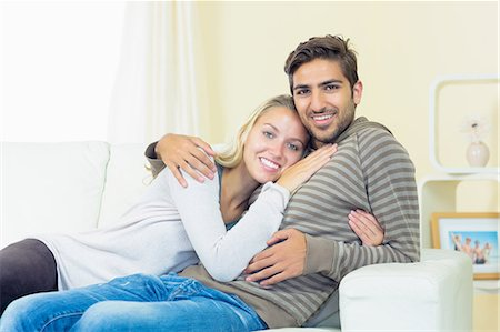 Sweet young couple sitting on a couch smiling at the camera Stock Photo - Premium Royalty-Free, Code: 6109-07497347