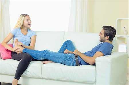 foot massage - Happy blonde woman massaging the feet of her boyfriend sitting in the living room Stock Photo - Premium Royalty-Free, Code: 6109-07497358