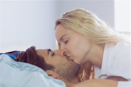 Intimate young couple kissing each other lying in the bed Stock Photo - Premium Royalty-Free, Code: 6109-07497311