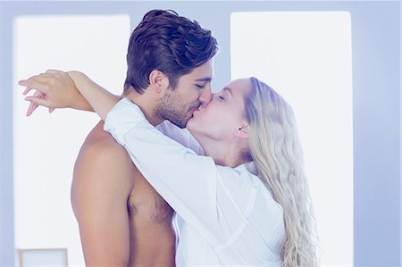 Beautiful woman embracing and kissing her boyfriend standing in the bedroom Stock Photo - Premium Royalty-Free, Code: 6109-07497322