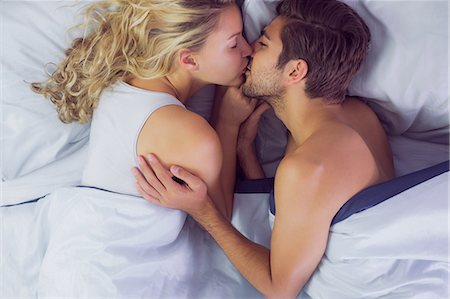 Cute young couple kissing each other while lying in their bed Stock Photo - Premium Royalty-Free, Code: 6109-07497335