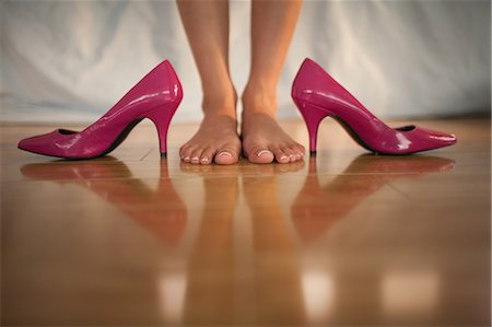 Woman standing beside bright pink high heels at home in bedroom Stock Photo - Premium Royalty-Free, Code: 6109-07497440