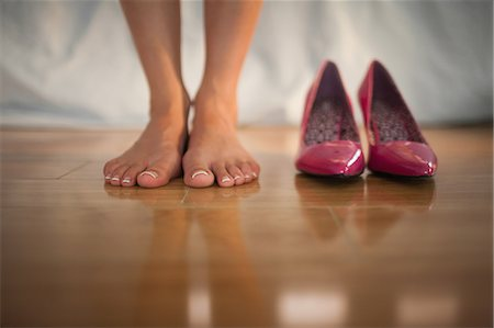 Woman standing beside pink high heels at home in bedroom Stock Photo - Premium Royalty-Free, Code: 6109-07497441