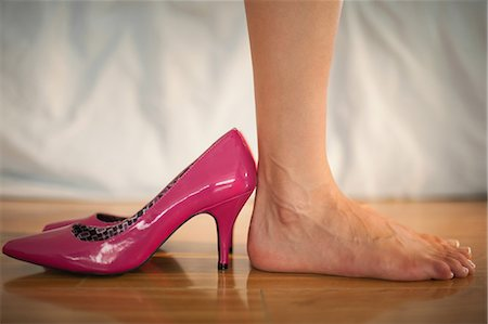 Woman standing beside fun pink high heels at home in bedroom Stock Photo - Premium Royalty-Free, Code: 6109-07497442