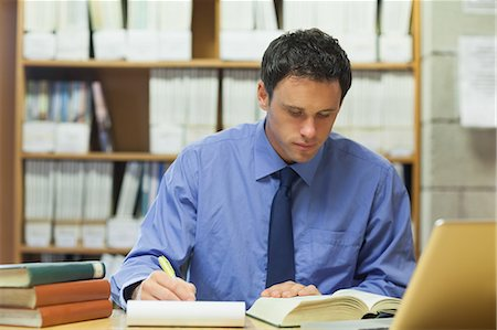 Calm librarian taking notes of a book in library in a college Stock Photo - Premium Royalty-Free, Code: 6109-07497455