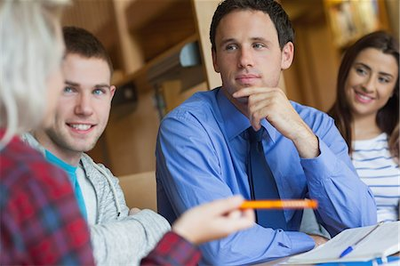 Focused lecturer explaining something to group of students in library in a college Stock Photo - Premium Royalty-Free, Code: 6109-07497485