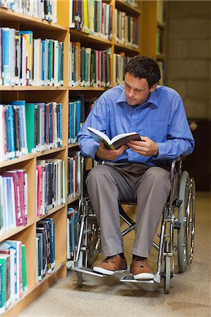 Concentrating man in wheelchair reading a book in library in a college Stock Photo - Premium Royalty-Free, Code: 6109-07497497