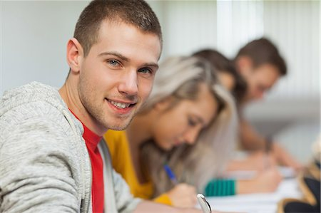 studying (all students) - Smiling attractive student looking at camera at college Stock Photo - Premium Royalty-Free, Code: 6109-07497543