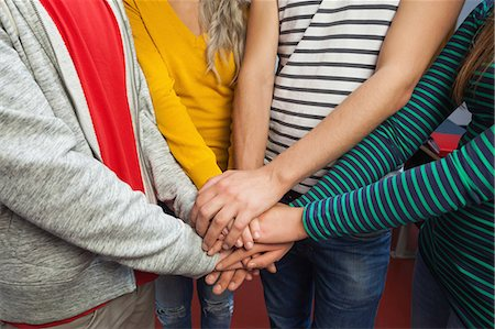 Close up of students holding hands together in hallway in a college Stock Photo - Premium Royalty-Free, Code: 6109-07497567
