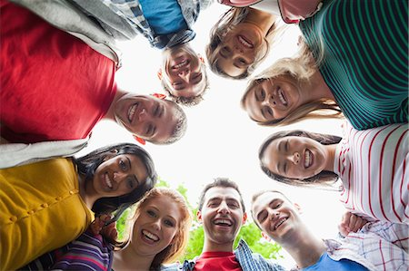 Group of students smiling down at camera in a circle on campus at the university Stock Photo - Premium Royalty-Free, Code: 6109-07497688
