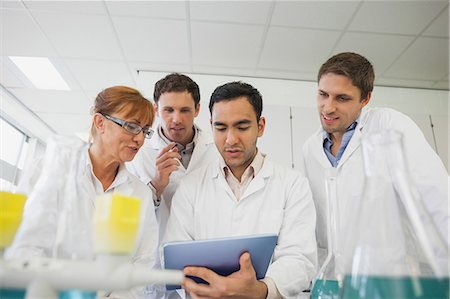 Low angle view of some scientists looking at a tablet standing in a laboratory Stock Photo - Premium Royalty-Free, Code: 6109-07497785