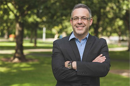 Happy professor looking at camera with arms folded on campusat the university Stock Photo - Premium Royalty-Free, Code: 6109-07497723