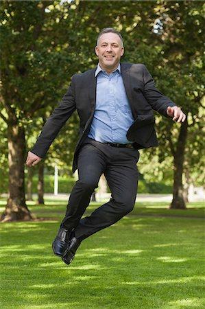 Joyful professor clicking his heels on campus at the university Stock Photo - Premium Royalty-Free, Code: 6109-07497720